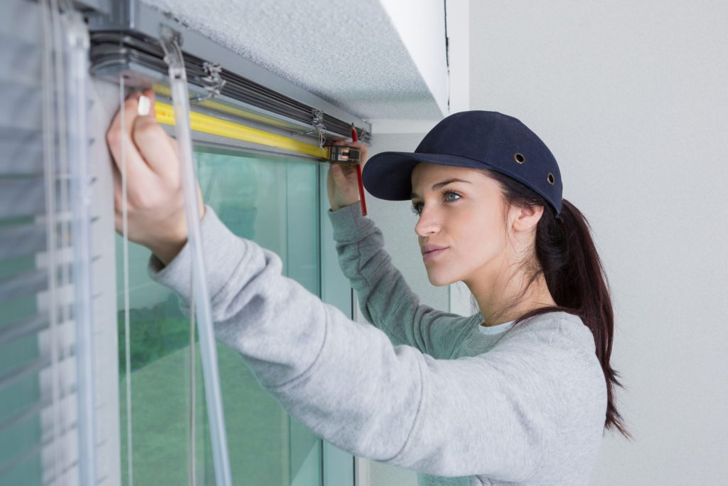 Woman measuring for window blinds